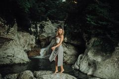 Estancia joven y atractiva de la mujer en el traje de baño que lleva de la roca en la cascada hermosa en la selva al lado de la c imagen de archivo libre de regalías