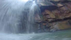 Estando e nadando sob uma cachoeira de derramamento com um guia local em Camboja, Kampot filme