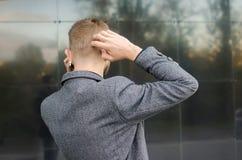 Estando para trás o homem que fala no telefone que risca pensativamente a cabeça Fotos de Stock