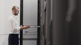 Estante abierto del servidor del hombre y el mecanografiar en el ordenador portátil en sitio del datacenter metrajes