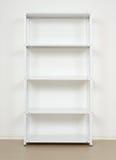 Estante cerca de la pared, estantes vacíos del metal blanco Foto de archivo libre de regalías