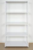 Estante cerca de la pared, estantes vacíos del metal blanco Imagen de archivo libre de regalías
