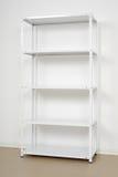Estante cerca de la pared, estantes vacíos del metal blanco Imagenes de archivo
