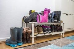 Estante con las botas y los zapatos sucios Foto de archivo libre de regalías