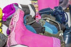 Estante con las botas y los zapatos sucios Imagen de archivo