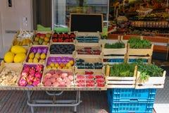 Estante con las frutas frescas y las hierbas en tienda de la verdulería Imagenes de archivo