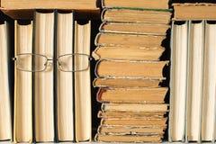Estante con una cara antropoide de algunos libros en vidrios con un manojo de libros lamentables viejos El concepto de lectura fotografía de archivo