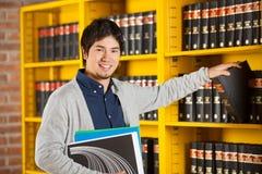 Estante de Choosing Book From del estudiante en biblioteca Imagen de archivo libre de regalías