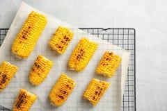 Estante de enfriamiento con las mazorcas de maíz asadas a la parrilla en fondo ligero imágenes de archivo libres de regalías