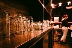 Estante de la barra con los vidrios de cerveza vacíos Foto de archivo