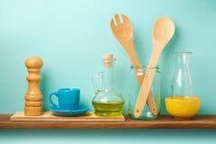 Estante de la cocina con los utensilios, la sal, la botella de aceite y la taza sobre fondo retro azul Fotografía de archivo libre de regalías