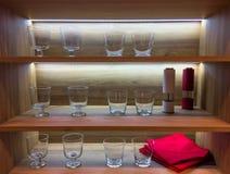 Estante de la cocina con los vidrios y el contraluz vacíos Imagen de archivo libre de regalías