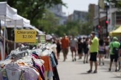 Estante de la liquidación de la ropa en la calle justa en verano Imagen de archivo