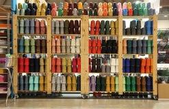 Estante de la mercería con las porciones de hilos y de guata Fotos de archivo