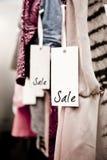 Estante de la ropa del boutique con la etiqueta de la venta Foto de archivo libre de regalías