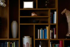 Estante de librería con la decoración tal como libros, tarro, caballo del cuero cabelludo, marco de las materias imágenes de archivo libres de regalías