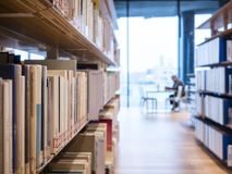 Estante de librería de la biblioteca con la educación interior de lectura de la gente fotos de archivo