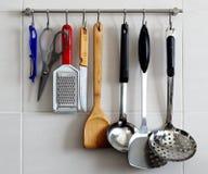 Estante de los utensilios de la cocina en la pared Fotos de archivo