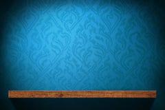 Estante de madera en blanco con el papel pintado retro azul imágenes de archivo libres de regalías