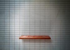 Estante de madera en la pared del azulejo. Fotografía de archivo