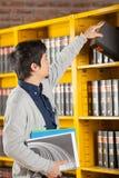 Estante de Taking Book From del estudiante en universidad Imágenes de archivo libres de regalías