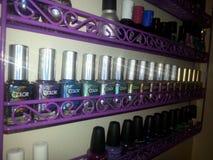 Estante del esmalte de uñas que ofrece tonalidades del halo del club del color Fotos de archivo