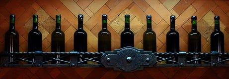 Estante del sótano con las botellas de vino tapadas con corcho oscuras contra la pared de madera marrón clara Imágenes de archivo libres de regalías