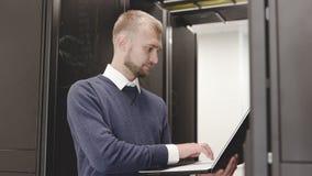 Estante del servidor del administrador que controla que mecanografía en el cierre del ordenador portátil para arriba almacen de video