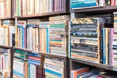 Estante en biblioteca con muchos libros de segunda mano viejos para la venta Imagenes de archivo
