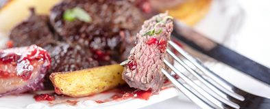 Estante fresco de la carne de venado en la tabla festiva en la placa blanca fotografía de archivo