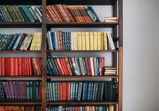 Estante para libros con los libros viejos en los estantes imagenes de archivo