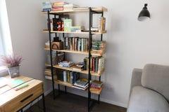 Estante para libros en la oficina equipada para el trabajo o el ocio en roo espacioso Foto de archivo libre de regalías