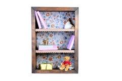 Estante pequena com livros e as estatuetas bonitos estante velha da antiguidade do vintage isolada no branco Fotografia de Stock