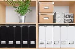 Estantes con las cajas, las carpetas y la planta verde Fotografía de archivo libre de regalías