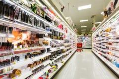 Estantes con los cosméticos en una tienda de la blanco Fotografía de archivo