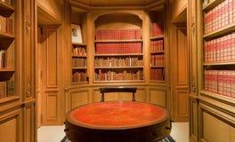 Estantes con los viejos volúmenes de libros y de mesa redonda antigua dentro de la biblioteca Fotografía de archivo