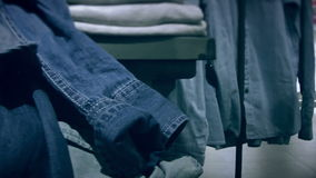 Estantes con ropa del dril de algodón en la tienda almacen de video