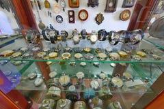 Estantes de cristal con un gran número de diversos movimientos del reloj Imagen de archivo libre de regalías