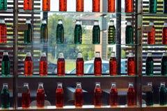 Estantes de cristal de la pared verde y roja de la botella en restaurante con la ventana de cristal en fondo fotos de archivo libres de regalías