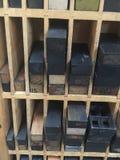 Estantes de madera del vintage de la madera de la prensa de copiar y cuñas y espaciadores del metal Fotografía de archivo