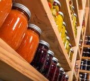 Estantes del almacenamiento con los alimentos enlatados Fotografía de archivo libre de regalías