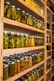 Estantes del almacenamiento con los alimentos enlatados foto de archivo