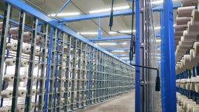 Estantes del metal con los ovillos blancos en ellos en una planta de materia textil almacen de video
