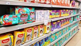 Estantes del supermercado con los productos del bebé: pañales imagenes de archivo