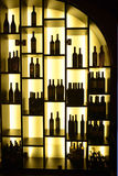 Estantes encendidos con las botellas de vino rojo, negocio Fotografía de archivo