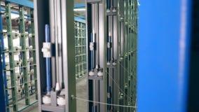 Estantes industriales con las bobinas, haciendo girar con los hilos almacen de video