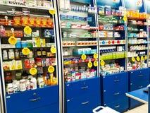 Estantes por completo con los medicamentos en tienda local de la farmacia foto de archivo libre de regalías