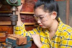 Estar das mulheres é madeira da broca do funcionamento do ofício foto de stock