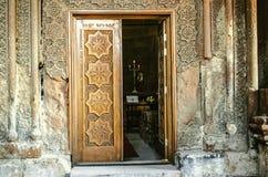 Estasi la porta di legno della chiesa con l'ornamento scolpito delle gente degli elementi Fotografia Stock