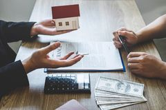 Estate agent broker reach contract form and presentation to client signing agreement contract real estate with approved mortgage royalty free stock image